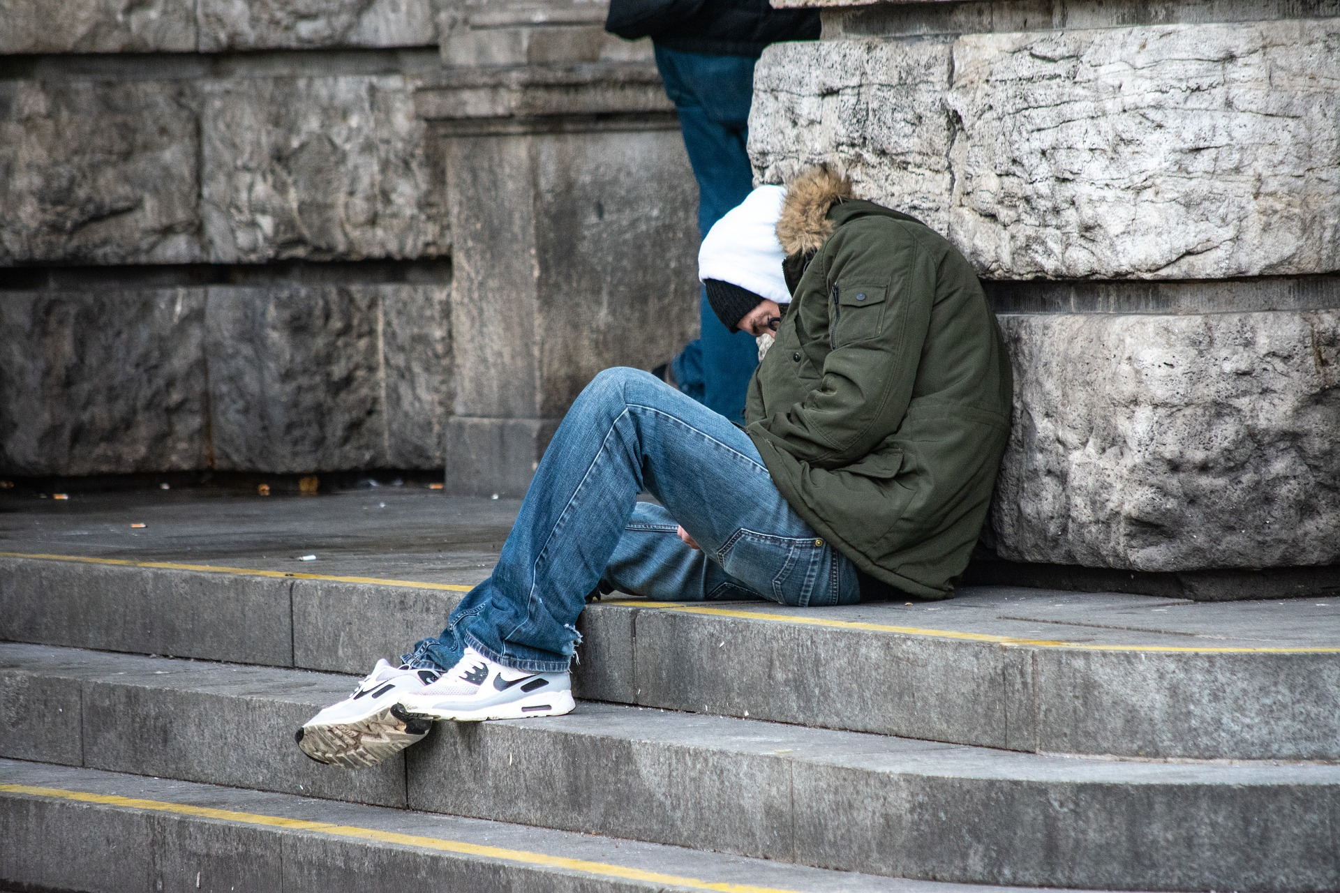A young man sits on the street with his hood up