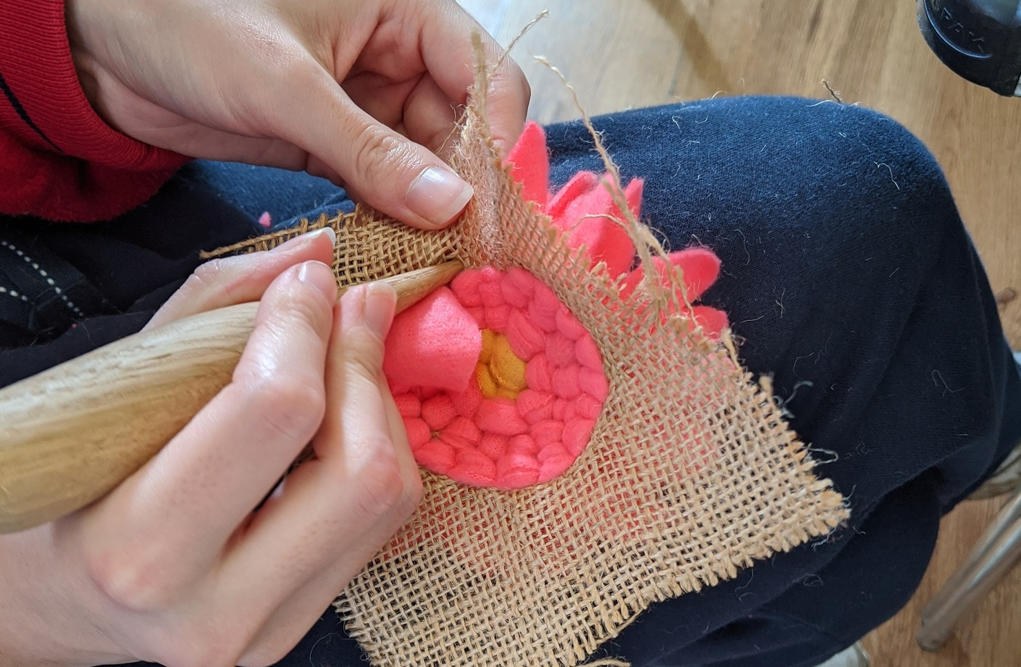 A woman's hands work on a bright pink craft flower