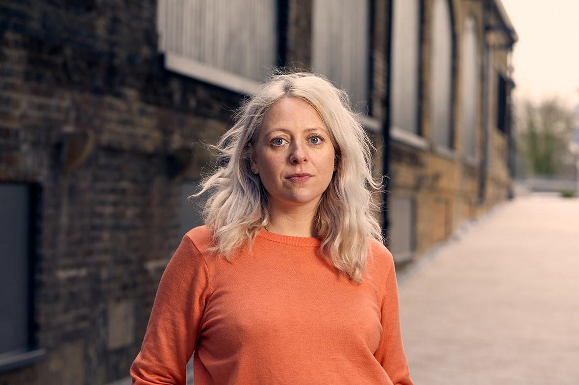 Artist Laura Wilson faces the camera - she has fair hair and an orange jumper on