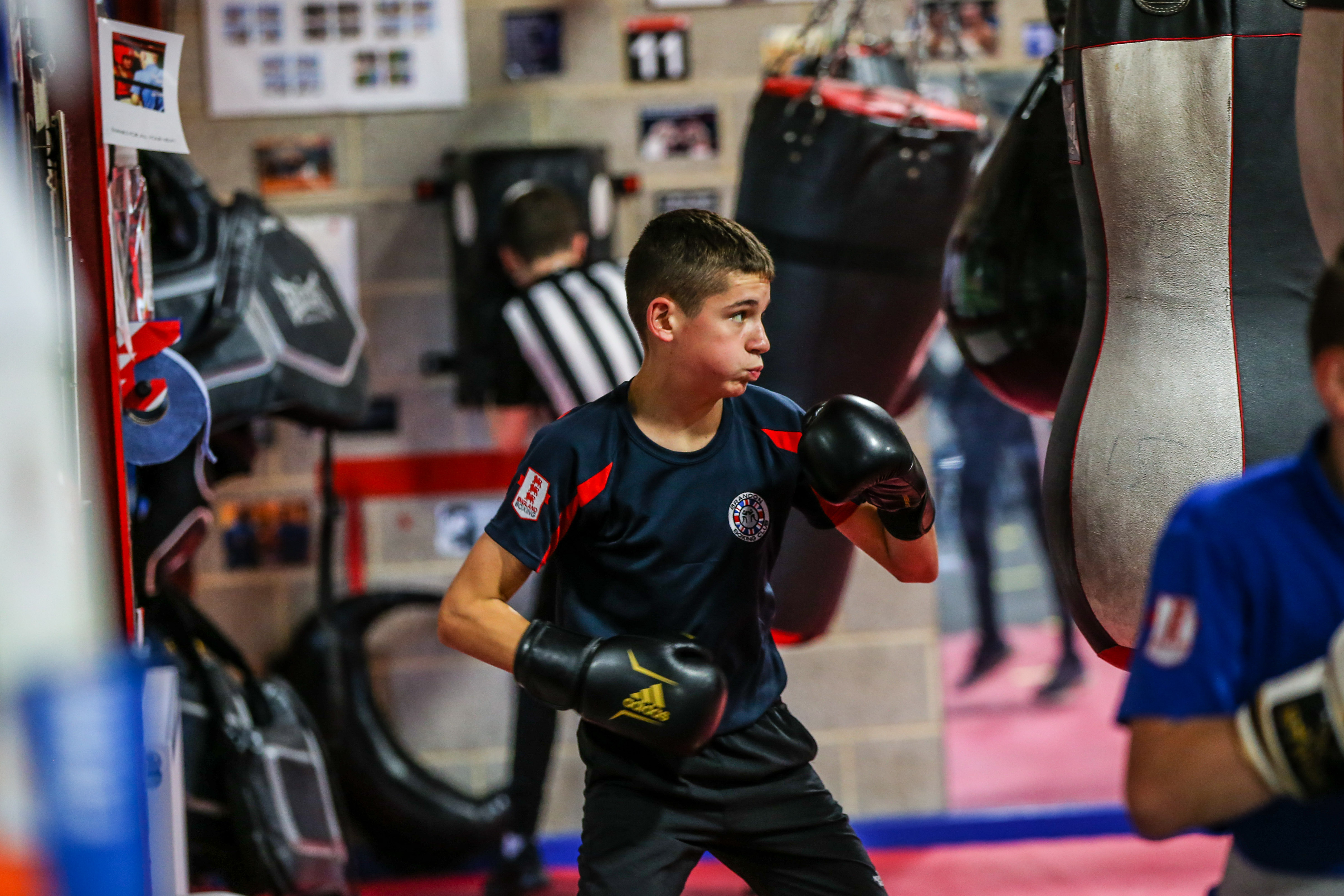 A young boy prepares to strike a boxing bag
