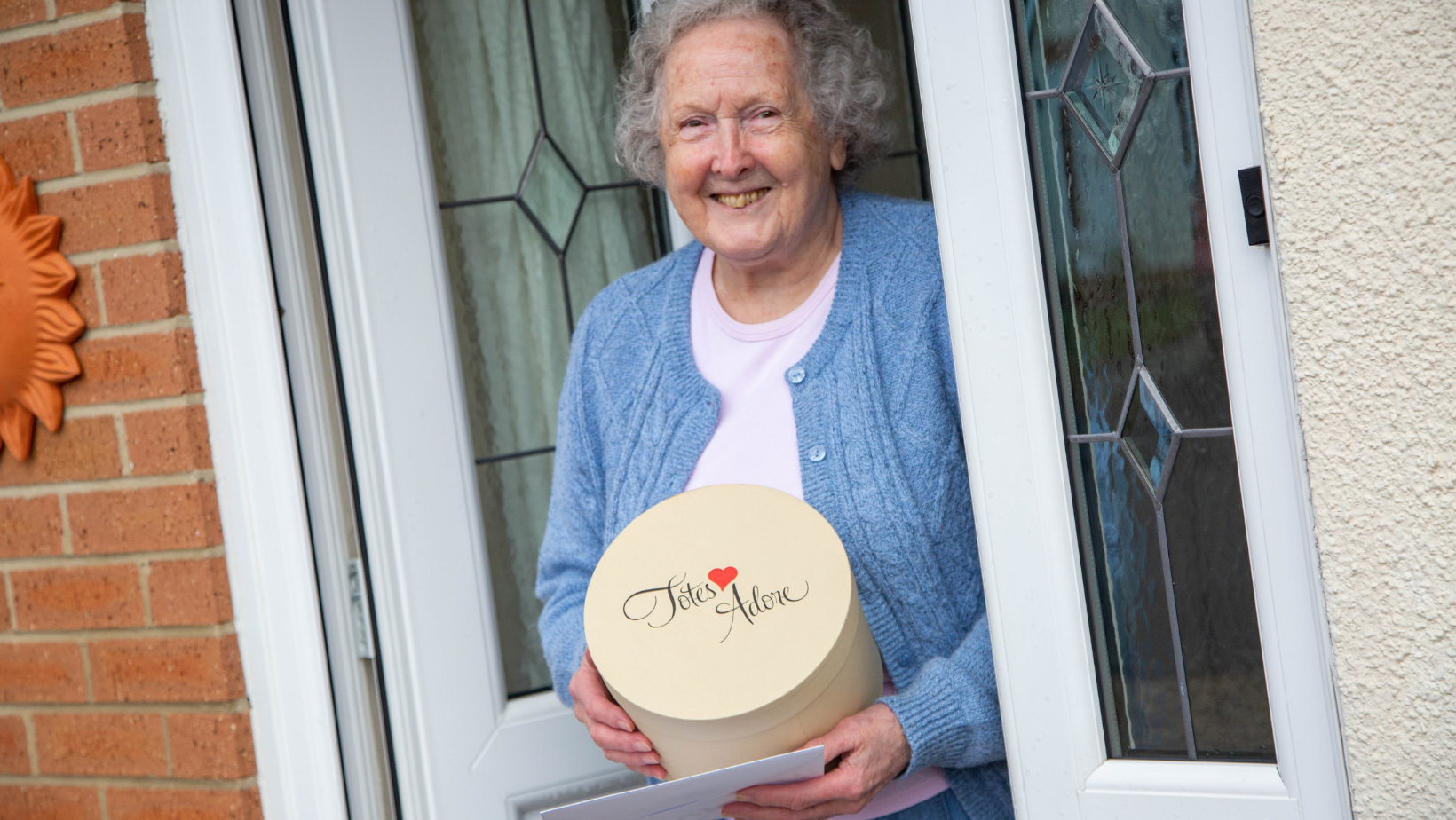 An older lady in a sky blue cardigan smiles as she stands at her front door with a craft pack delivered by volunteers